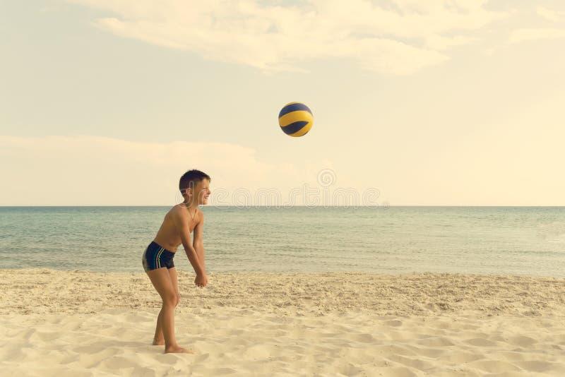 Bola que juega y de funcionamiento del muchacho del valleyball en la playa del mar fotografía de archivo libre de regalías