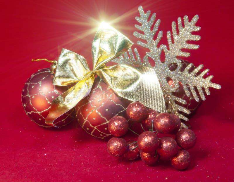 Bola roja del Año Nuevo, bayas decorativas y copo de nieve foto de archivo
