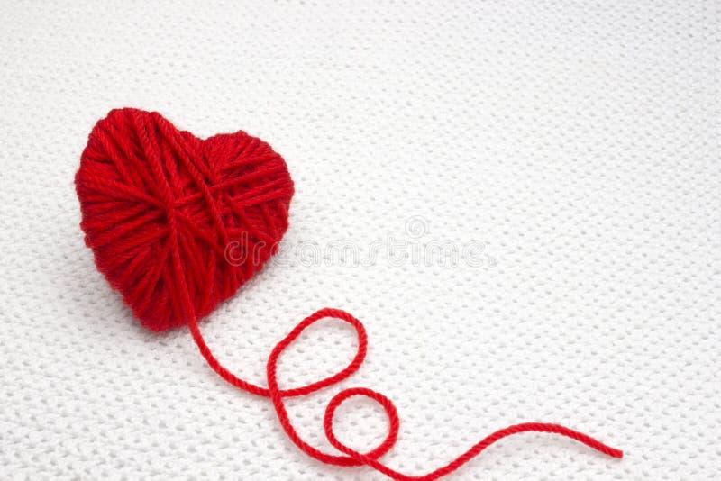 Bola roja del hilado como un corazón en el fondo blanco del ganchillo Concepto romántico del día de tarjetas del día de San Valen foto de archivo libre de regalías
