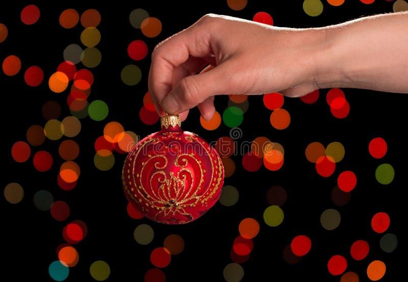 Bola roja del ` s del Año Nuevo con los modelos a disposición, en fondo oscuro foto de archivo