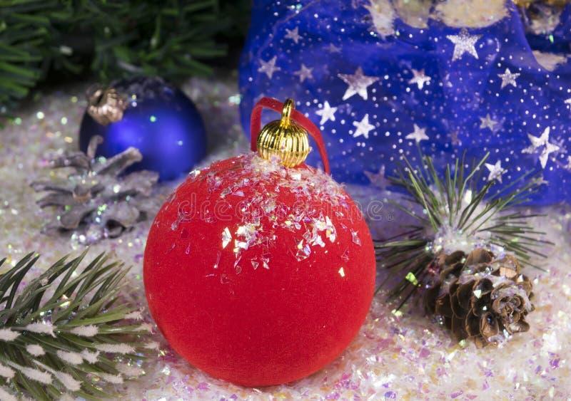 Bola roja del ` s del Año Nuevo en nieve decorativa y un bolso con el regalo fotos de archivo
