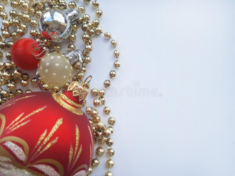 Bola roja grande y algunas pequeñas bolas en un fondo blanco Juguetes de la Navidad en un fondo blanco Guirnaldas y bolas foto de archivo