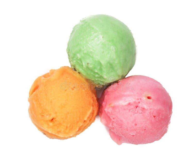 Bola roja y amarilla verde del helado aislada en el fondo blanco, visión superior imagen de archivo