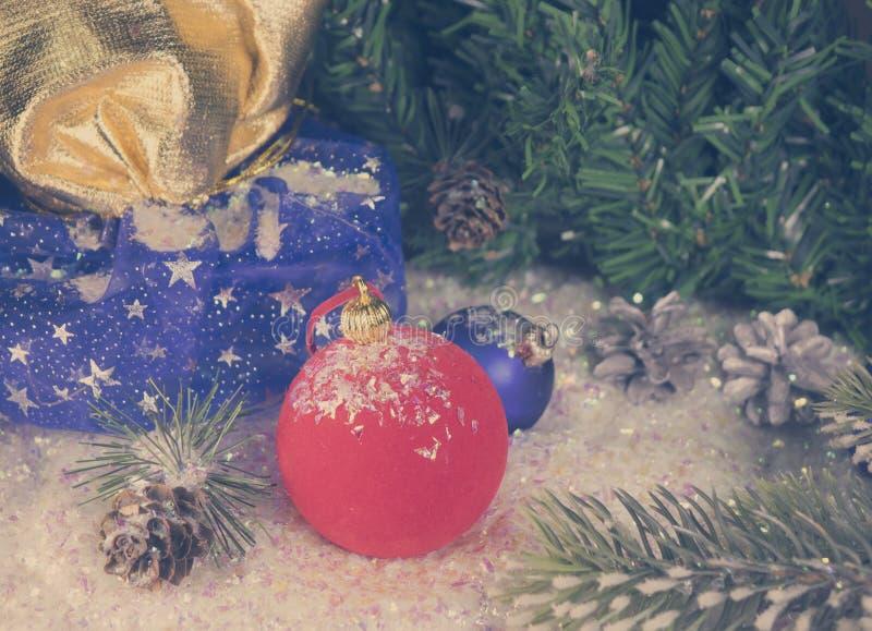 Bola roja y azul del ` s del Año Nuevo en nieve decorativa y un bolso con el regalo, efecto retro imagen de archivo libre de regalías