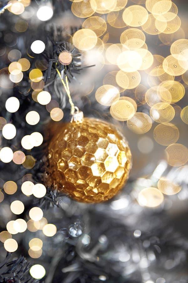 Bola textured brilhante dourada na árvore de Natal foto de stock