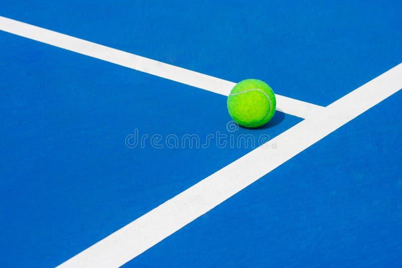 Bola verde que cai nas linhas quase brancas do assoalho de parque duro da corte do tênis azul exterior em público foto de stock
