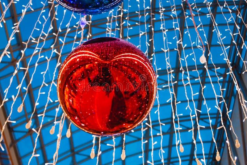 Bola vermelha do Natal brilhante enorme que pendura na alameda imagem de stock