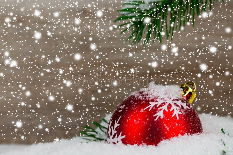 Bola vermelha do Natal com flocos da neve e ramo verde imagens de stock