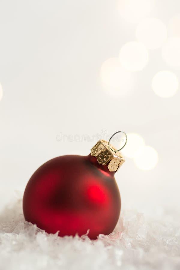 Bola vermelha do ornamento da árvore de Natal na neve em luzes douradas do bokeh da festão da floresta do inverno Árvore congelad fotos de stock royalty free