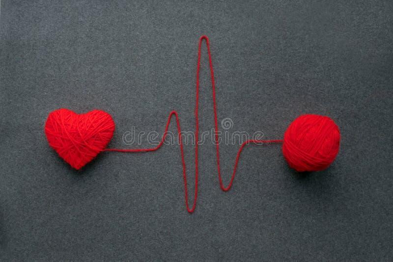 Bola vermelha feito a mão do fio com o coração feito do fio de lãs e do thre vermelhos fotografia de stock royalty free