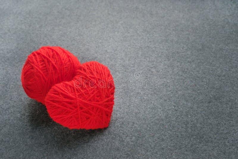 Bola vermelha feito a mão do fio com o coração feito do fio de lãs vermelho em um gra imagem de stock royalty free