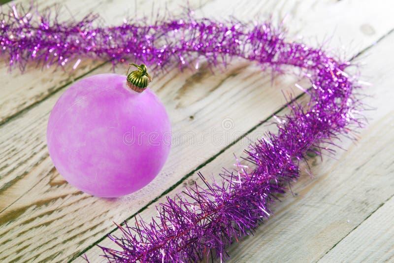 Bola y malla rosadas del ` s del Año Nuevo en un tablero de madera fotografía de archivo libre de regalías