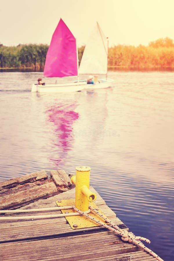Bolardo en el embarcadero de madera con los veleros en distancia imagen de archivo libre de regalías