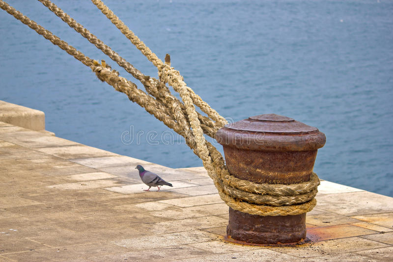 Bolardo oxidado de la amarradura con las cuerdas de la nave imagenes de archivo