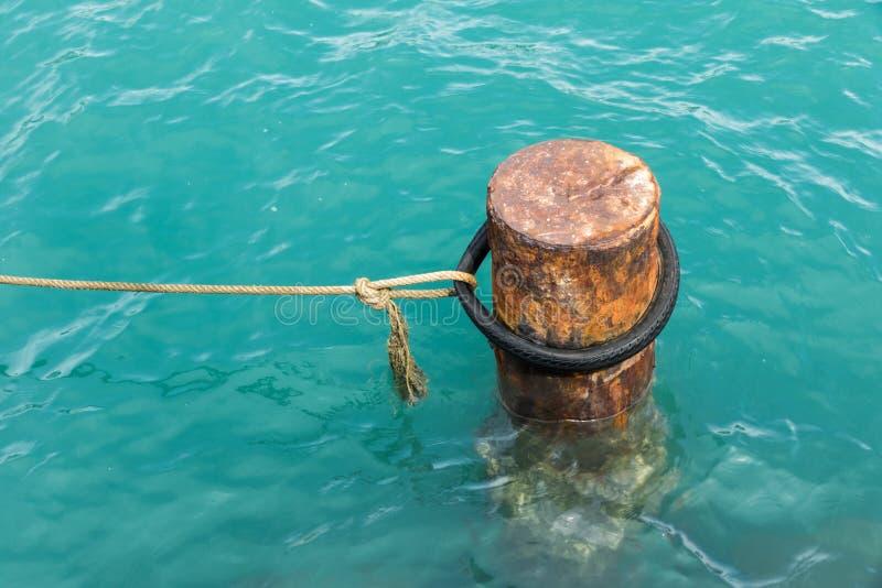 Bolardo oxidado de la amarradura con las cuerdas de la nave fotografía de archivo libre de regalías