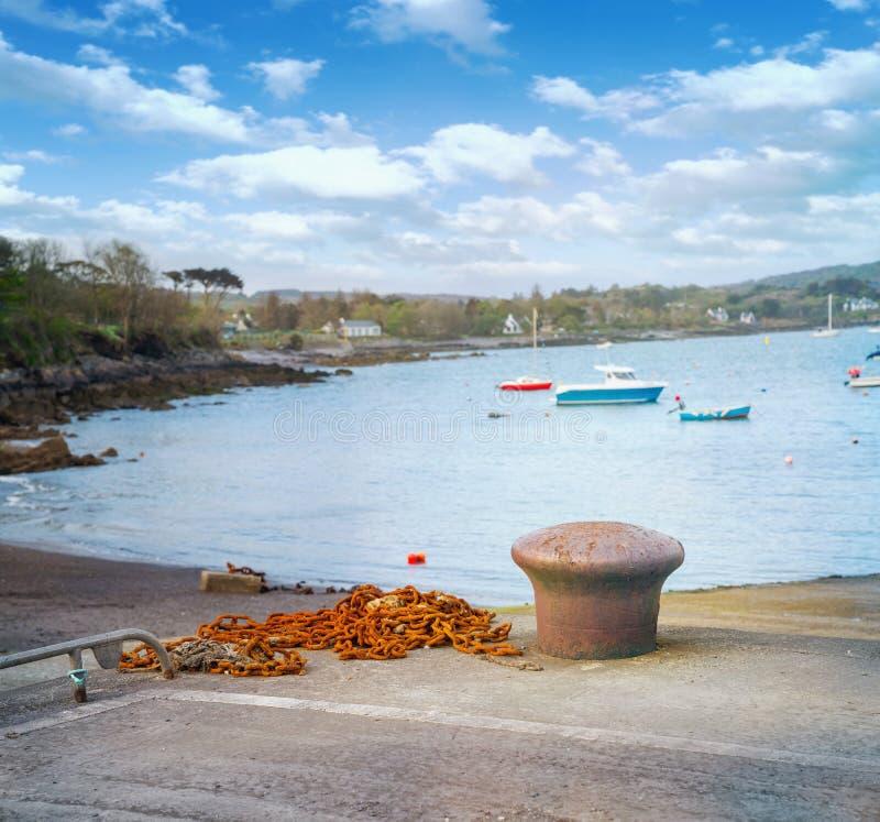 Bolardo que amarra marino oxidado y cadena oxidada en un puerto de Castletownbere foto de archivo libre de regalías