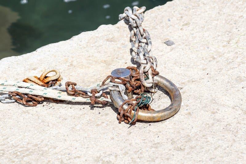 Bolardo que amarra oxidado del metal viejo con una cadena imagenes de archivo