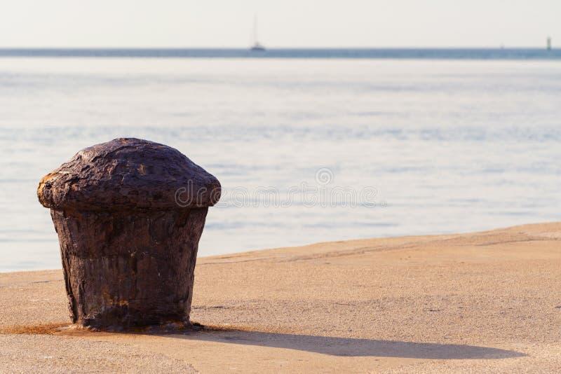 Bolardo que amarra oxidado en el embarcadero concreto con el mar azul con el velero en horizonte imagenes de archivo