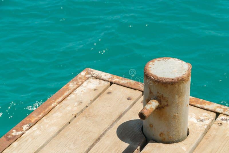 Bolardo viejo, oxidado con la cadena del metal en el embarcadero con agua fotos de archivo libres de regalías