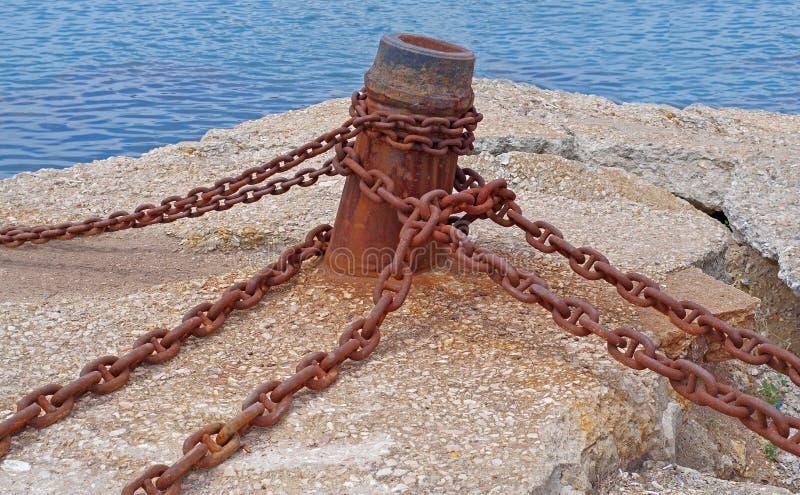 Bolardo y cadena oxidada vieja en el embarcadero fotografía de archivo