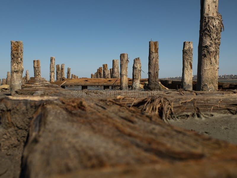 Bolardos de madera en la arena contra el estuario y el cielo azul estuario kuyalnitsky fotografía de archivo
