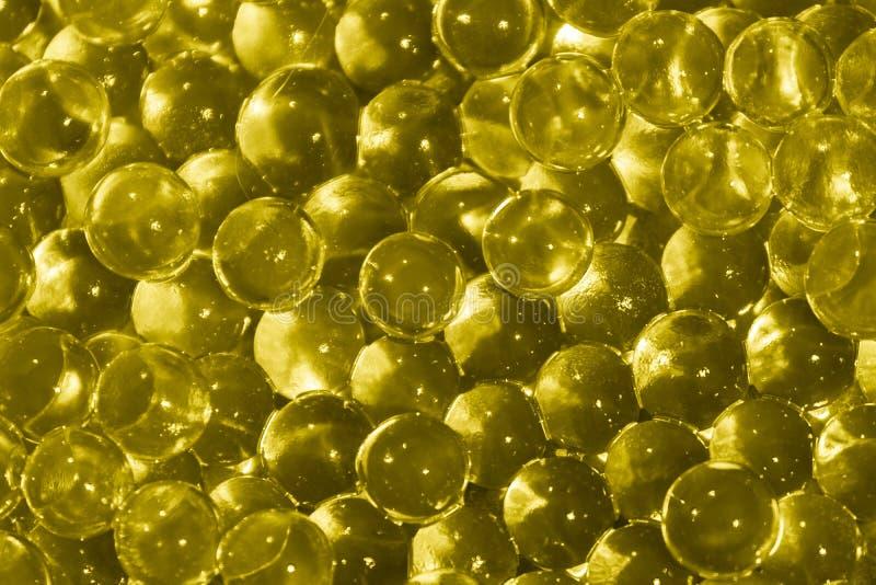 Bolas amarillas transparentes del hidrogel Bolas amarillas del gel del agua con el bokeh Gel de silicona del gel del pol?mero Bol foto de archivo