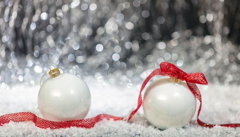 Bolas blancas de la Navidad, cinta roja y nieve, luces abstractas del bokeh imagen de archivo libre de regalías