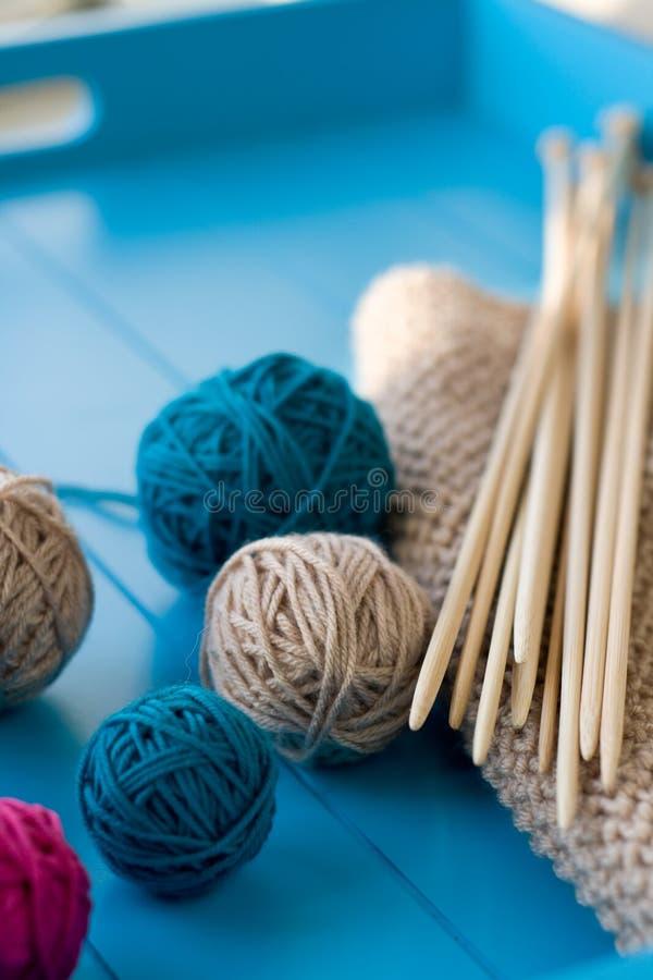 Bolas brilhantes do fio, agulhas de confecção de malhas de madeira, cobertura feita malha foto de stock royalty free