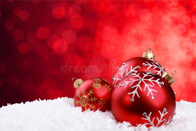 Bolas brilhantes vermelhas do Natal nos flocos de neve fotografia de stock royalty free