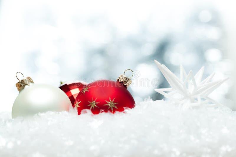 Bolas brilhantes vermelhas do Natal nos flocos de neve fotos de stock