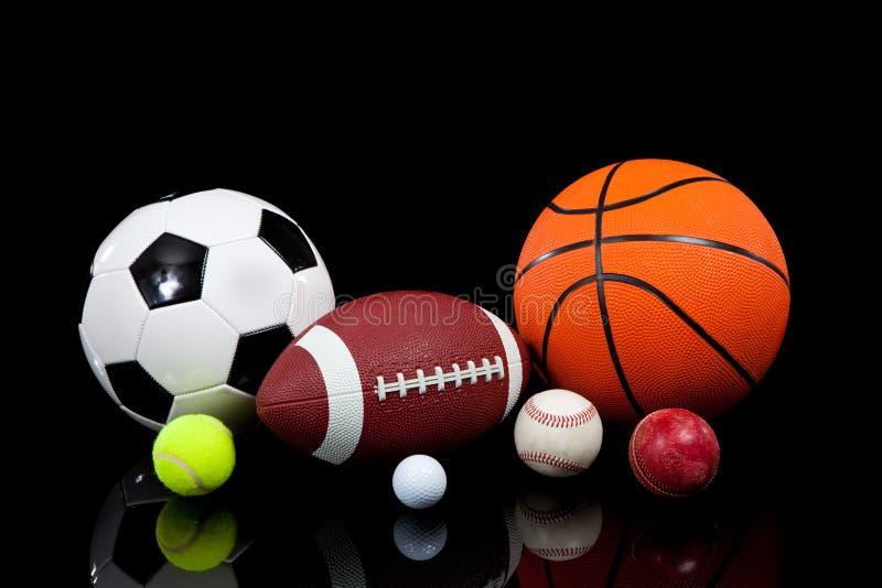 Bolas clasificadas de los deportes en un fondo negro imagen de archivo