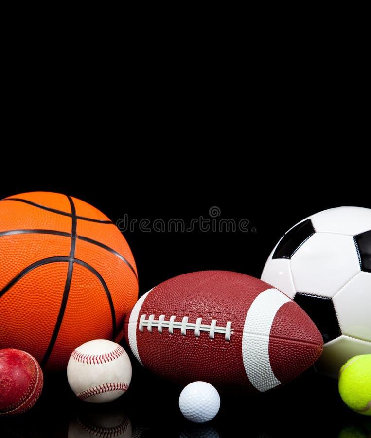 Bolas clasificadas de los deportes en un fondo negro foto de archivo