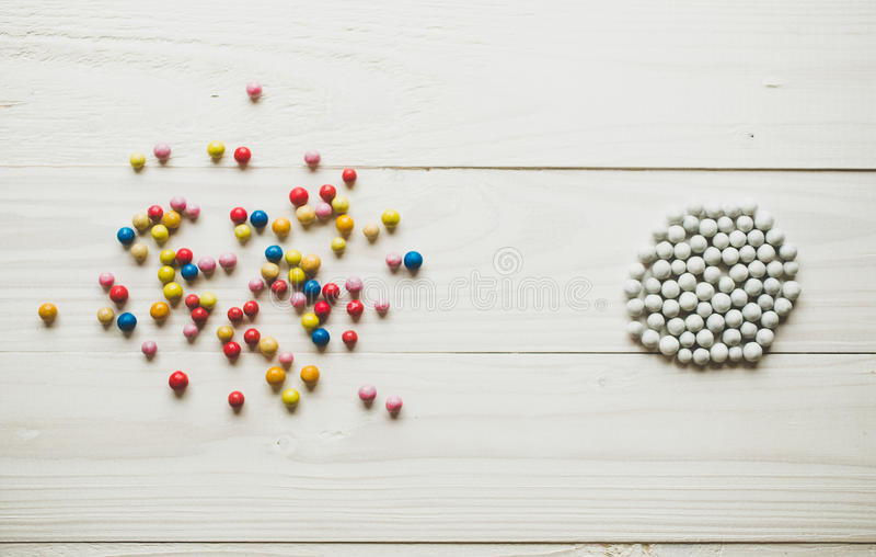 Bolas coloridas caóticas y bolas blancas organizadas Conceptual de imágenes de archivo libres de regalías