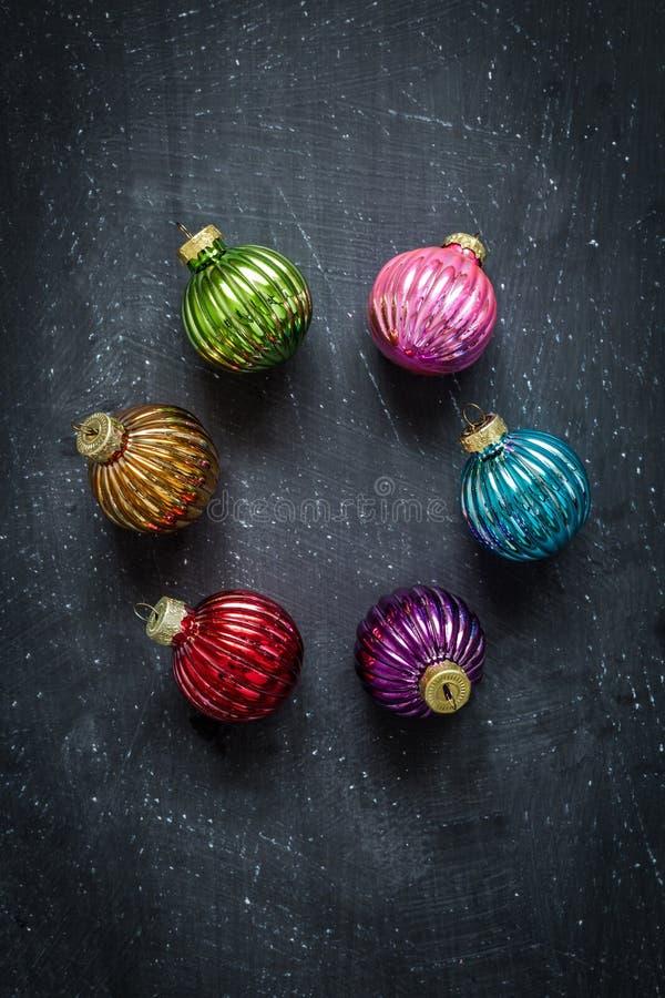 Bolas coloridas de la Navidad en la pizarra negra desde arriba foto de archivo