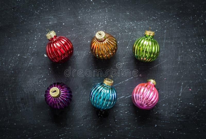 Bolas coloridas de la Navidad en la pizarra negra desde arriba fotografía de archivo