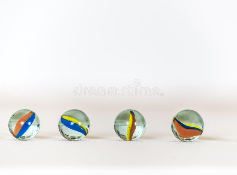 Bolas, coloridas de mármol y en el fondo blanco imagen de archivo