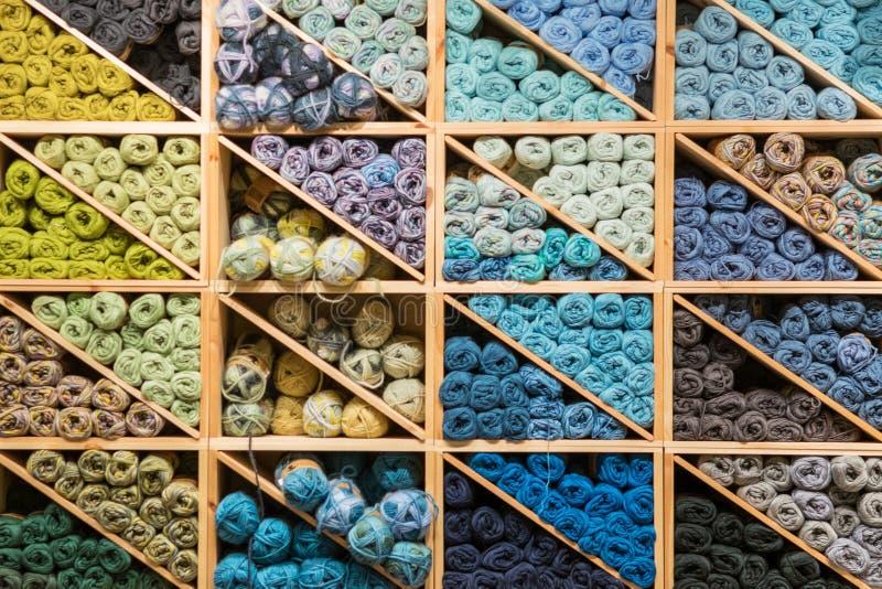 Bolas coloridas do fio armazenadas em prateleiras Todas as cores Fio de lã para fazer malha Skeins do preto escuro para amarelar  imagens de stock royalty free