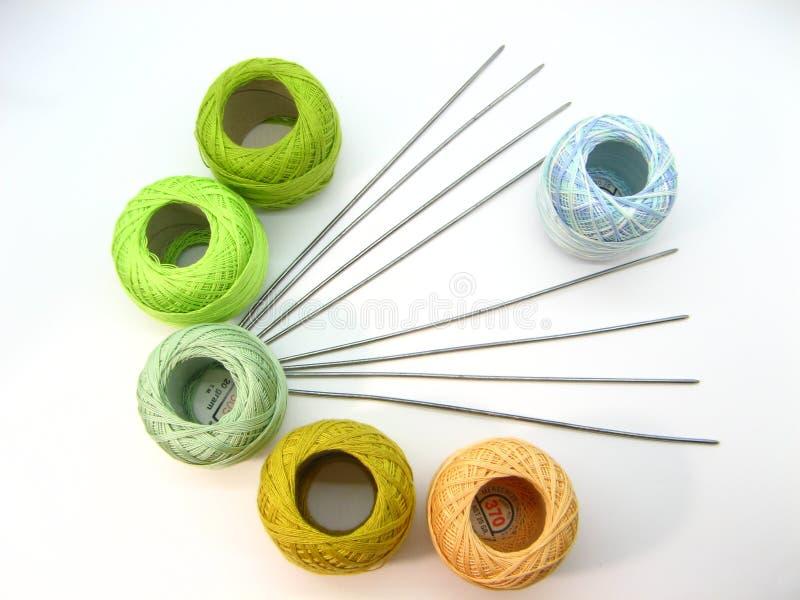Bolas de algodón coloreadas con los hilos que hacen punto en un fondo blanco imágenes de archivo libres de regalías