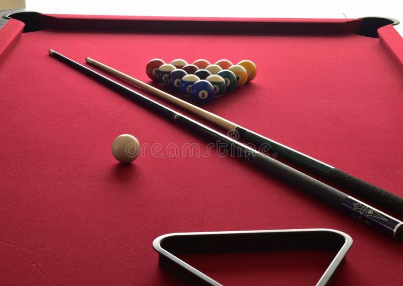 Bolas de billar en una mesa de billar roja con dos señales, un estante negro de la bola y una bola de señal blanca fotos de archivo