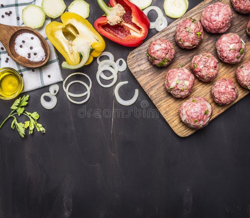 Bolas de carne com ervas e cebolas em uma placa de corte com vegetais, especiarias, óleo, colher de madeira do vintage no fundo r imagens de stock