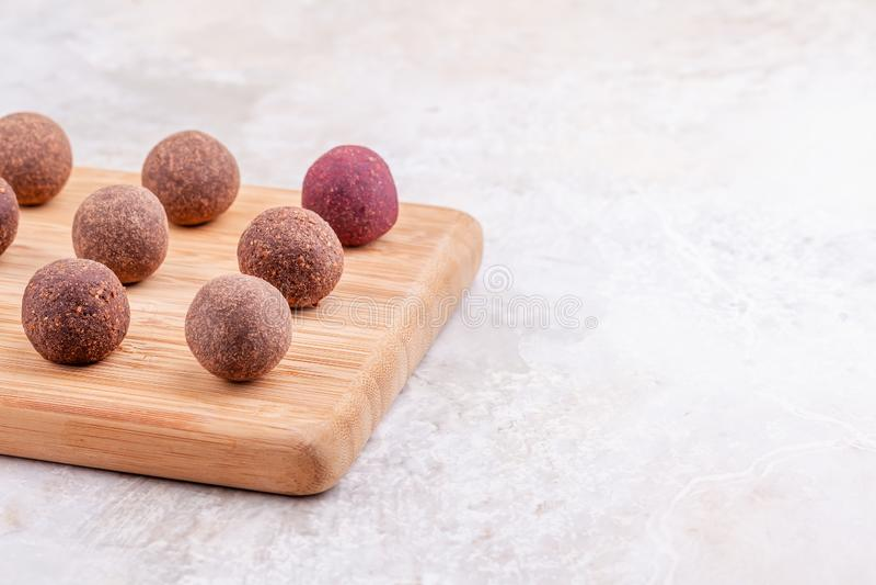 Bolas de Energia do Vegan Cacao, caseiro, em bruto, em uma bandeja de madeira em fundo branco de mármore fotografia de stock