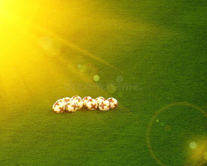 Bolas de futebol na grama no estádio de futebol Halo da luz de Sun com os alargamentos brilhantes da lente toned fotos de stock