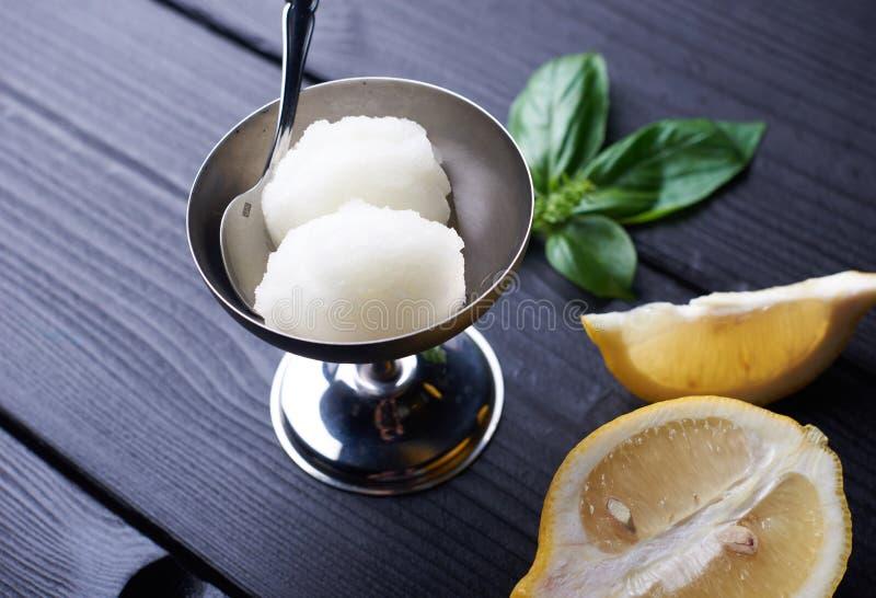 2 bolas de helado hecho en casa del sorbete del limón en metal ruedan en fondo de madera negro Postre sabroso del verano imagen de archivo