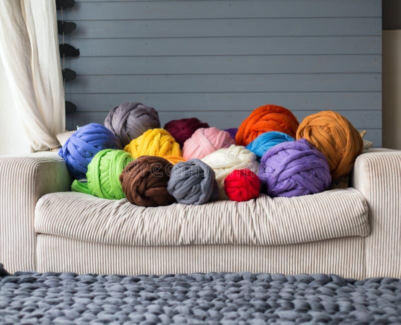 Bolas de la lana merina en la mentira multicolora en el sofá blanco con el merino imagen de archivo
