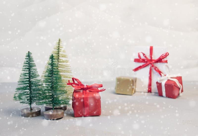 Bolas de la Navidad, cajas de regalo y árbol de abeto rojos en nieve imagen de archivo