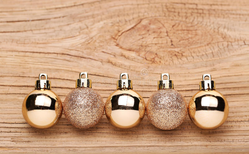 Bolas de la Navidad del oro sobre fondo de madera fotos de archivo