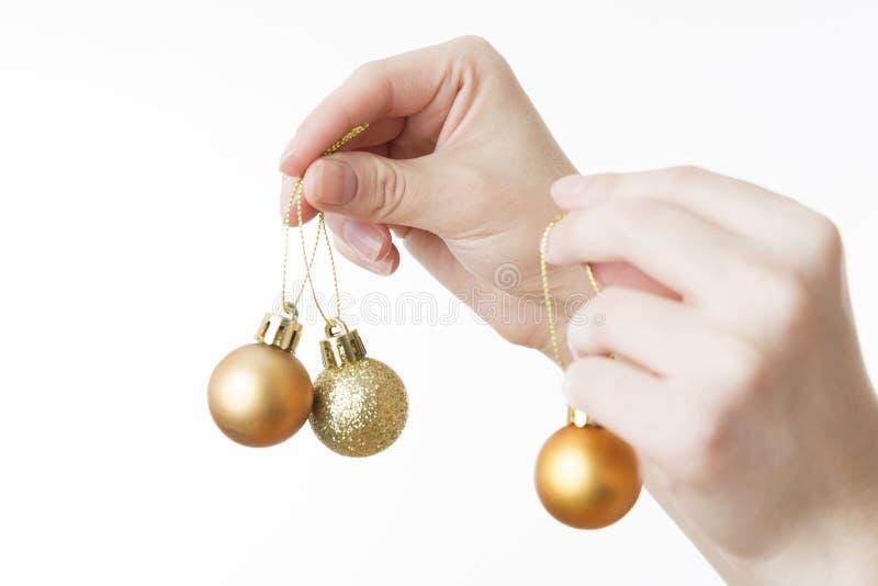 Bolas de la Navidad en manos femeninas en un fondo blanco imagen de archivo