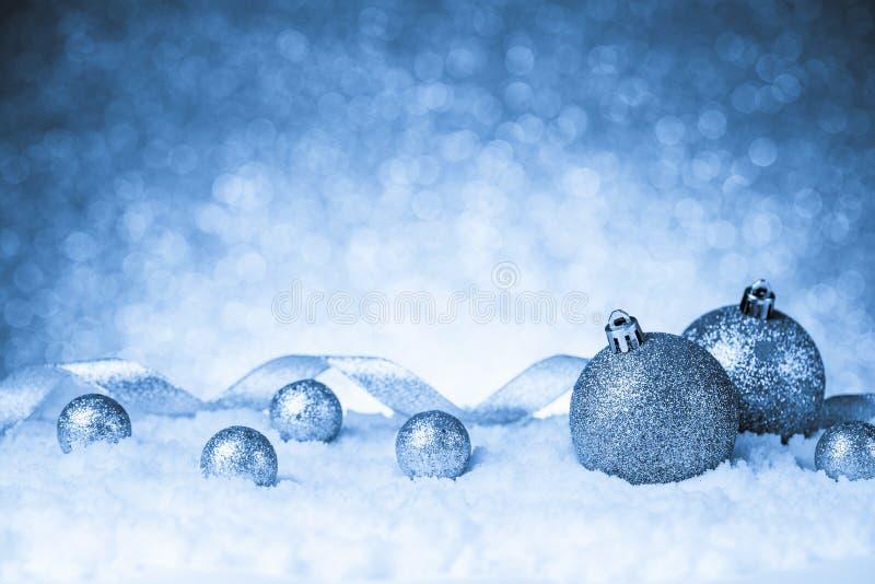 Bolas de la Navidad en nieve en fondo del brillo foto de archivo