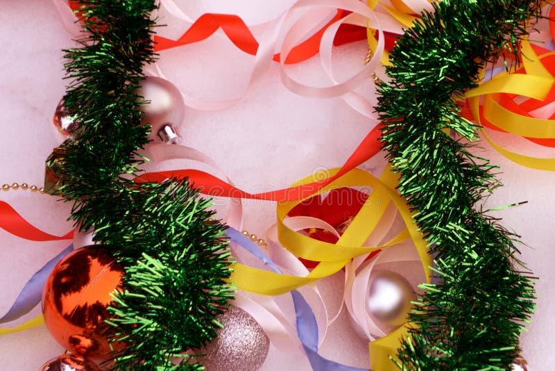 Bolas de la Navidad, rama del abeto, campana y cinta de la serpentina en la nieve foto de archivo