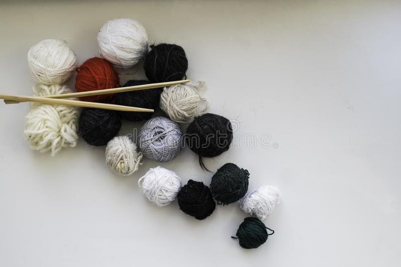 Bolas de lana y agujas que hacen punto de madera en el fondo neutral Endecha plana imagenes de archivo
